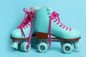 Pair of stylish quad roller skates on color background.