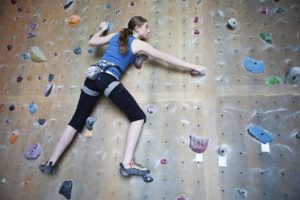 Female teenage rock climber scaling a wall