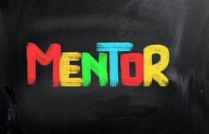 "The word ""Mentor"" written in different colored chalk on a chalk board"